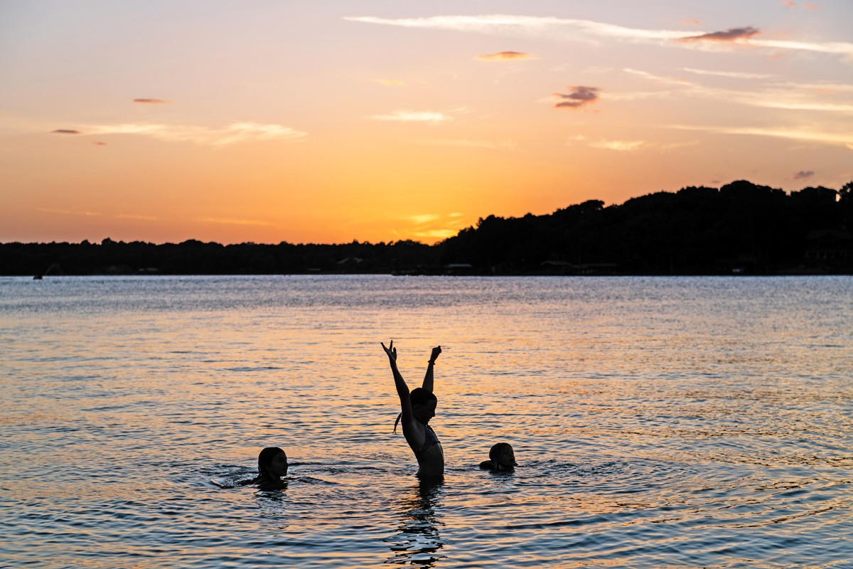 3 kids swimming in cedar creek lake at sunset