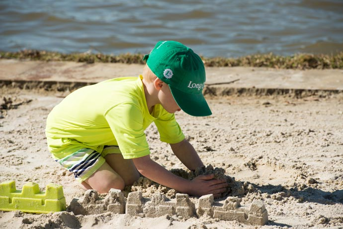 child in green long cove cap building sandcastle on shore of Cedar Creek Lake beach
