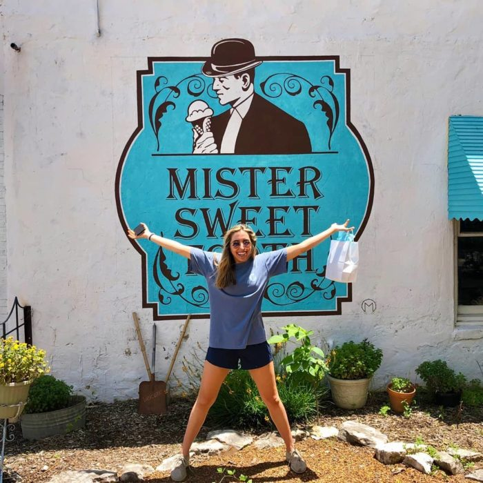 Woman in front of Mister Sweet Tooth sign