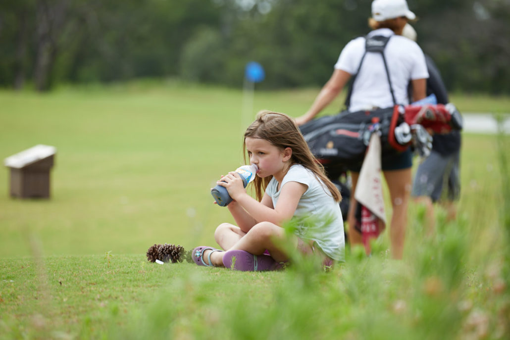 Little girl taking a break on the golf course at Long Cove